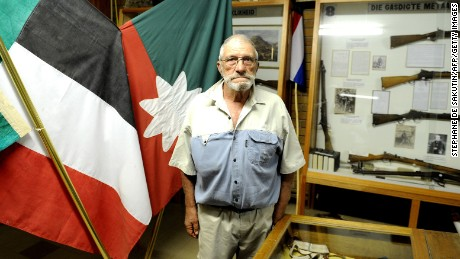 "South African Afrikaner curator of Orania Museum, Gideon de Kock poses on April 17, 2013 in Orania. Orania is a South Africa's only ""purely"" white town founded in the Northern Cape province in 1991 by Afrikaners, for Afrikaners opposed to the post-apartheid ""rainbow nation"", just after the release of Nelson Mandela. One thousand people live in Orania, and they try to be as self sufficient as possible. They have their own money, as well as their own flag. Orania's population grows at nine percent a year. It attracts Afrikaners who feel to be left out in the new South Africa, and who are scared of the country's high crime rates. The little town is protected by article 235 of South Africa's constitution, which guarantees the right of self determination. But residents here are thinking big - their next goal, the creation of an Afrikaner Republic. AFP PHOTO / STEPHANE DE SAKUTIN        (Photo credit should read STEPHANE DE SAKUTIN/AFP/Getty Images)"