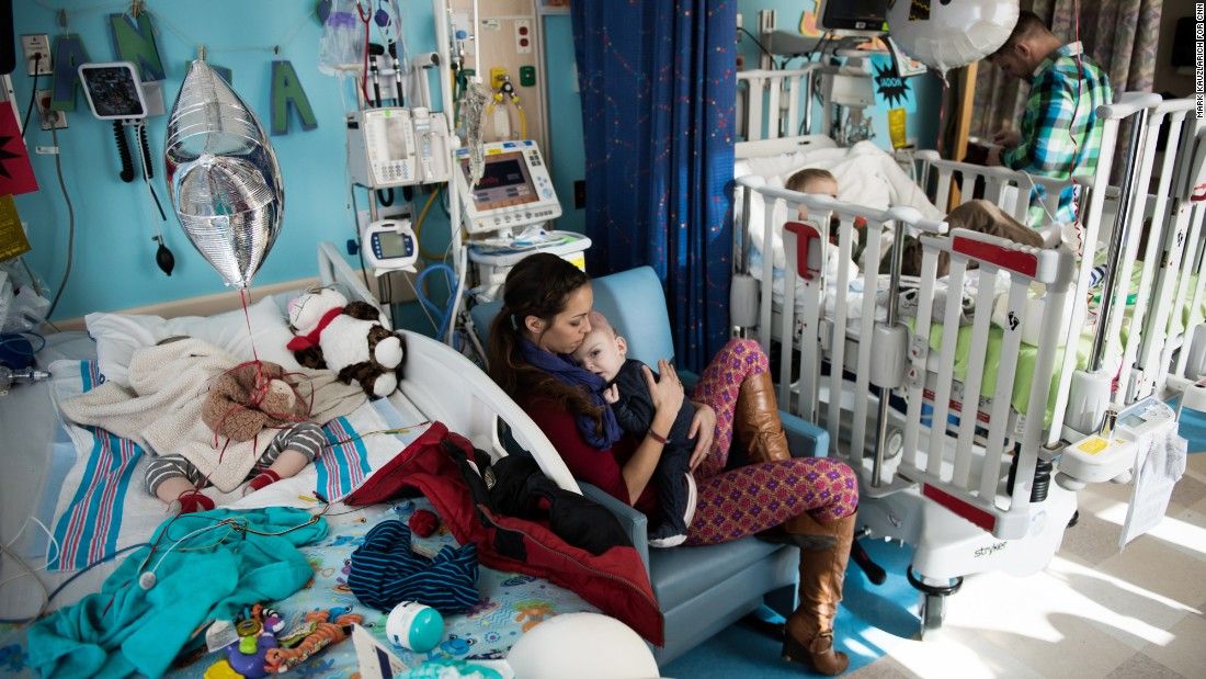 Nicole McDonald holds Anias as his twin brother, Jadon, sleeps in the bed to the left. The twins' older brother, Aza, watches television at the hospital from one of the boys' beds shortly before they leave.