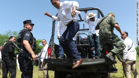 The Governor of the state of Michoacan, Silvano Aureoles (C) jumps from the back of a military utility car after making a speech  on September 7, 2016 in El Chauz, Michoacan State, Mexico, near the place where a police helicopter participating in an operation to capture leaders of an unidentified criminal group was shot down on the eve. Authorities hunted on Wednesday for gang suspects who shot down a helicopter carrying police in western Mexico, killing four aboard in a clash highlighting the government's struggle to quell violence in the region. / AFP / Pedro Pardo        (Photo credit should read PEDRO PARDO/AFP/Getty Images)