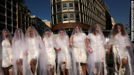 "Activists from the Lebanese NGO Abaad (Dimensions), a resource centre for gender equality, dressed as brides and wearing injury patches hold a protest in downtown Beirut on December 6, 2016, against article 522 in the Lebanese penal code.  The article shields rapists from prosecution on the condition that they marry their victim, a phenomenon that is still practised in the country, especially among conservative families whose chief aim is to preserve the family's so-called ""honour."" / AFP / PATRICK BAZ        (Photo credit should read PATRICK BAZ/AFP/Getty Images)"