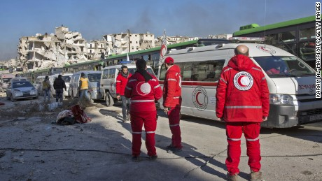 Staff of the Syrian Red Crescent are seen during an evacuation operation of rebel fighters and their families from rebel-held neighbourhoods in the embattled city of Aleppo on December 15, 2016. A convoy of ambulances and buses left rebel territory in Aleppo in the first evacuations under a deal for opposition fighters to leave the city after years of fighting. The rebel withdrawal will pave the way for President Bashar al-Assad's forces to reclaim complete control of Syria's second city, handing the regime its biggest victory in more than five years of civil war.      / AFP / KARAM AL-MASRI        (Photo credit should read KARAM AL-MASRI/AFP/Getty Images)