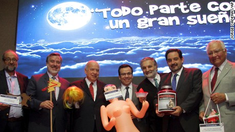 Chile Economy Minister Luis Cespedes poses with other lawmakers with a gift of an inflated sex toy.
