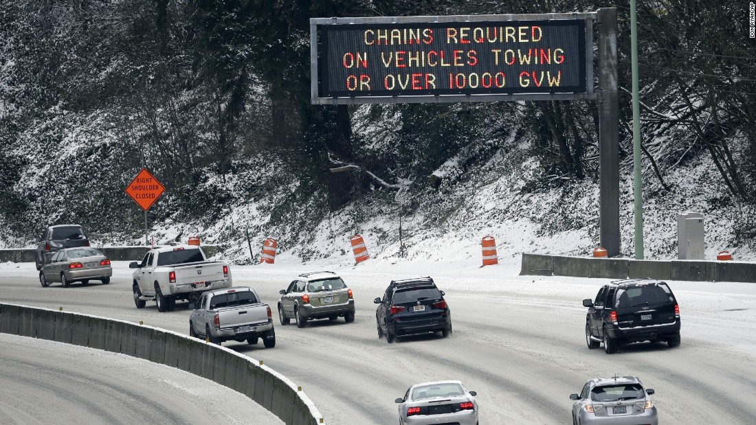Commuters travel under a warning sign as they work their way down Highway 26 in Portland, Oregon, on Thursday, December 15.