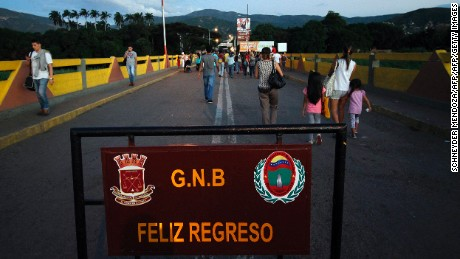 """People cross the Simon Bolivar bridge in Norte de Santander department, Colombia in the border with Venezuela, on December 11, 2016. Venezuelan President Nicolas Maduro on Sunday signed an emergency decree ordering the country's largest banknote, the 100 bolivar bill, taken out of circulation to thwart """"mafias"""" he accused of hoarding cash in Colombia. / AFP / SCHNEYDER MENDOZA        (Photo credit should read SCHNEYDER MENDOZA/AFP/Getty Images)"""