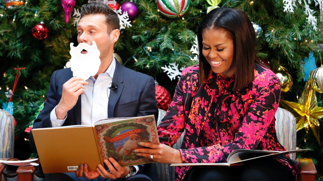 "First lady Michelle Obama and television personality Ryan Seacrest read ""Twas the Night Before Christmas"" while visiting children at a Washington hospital on Monday, December 12."
