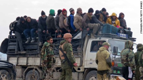 Syrian government forces and Russian soldiers keep watch as civilians and fighters are evacuated from a rebel-held area of Aleppo towards rebel-held territory in the west of Aleppo's province on December 16, 2016. Russia announced it was negotiating with the Syrian opposition and seeking a nationwide ceasefire, as the evacuation of civilians and fighters from the last rebel-held parts of Aleppo entered a second day. The Syrian Observatory for Human Rights, a Britain-based monitor of the war, estimated some 8,500 people had left so far, including around 3,000 rebel fighters. Syrian state media reported a figure of around 8,000. / AFP / STRINGER        (Photo credit should read STRINGER/AFP/Getty Images)