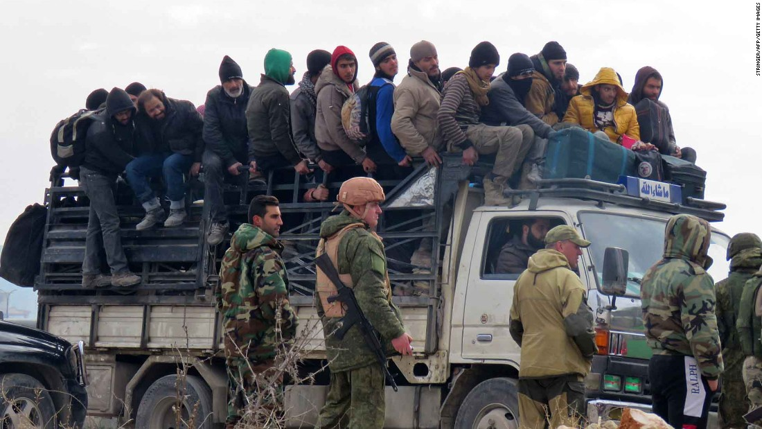 Russian soldiers and Syrian pro-government forces look on as civilians and rebel fighters are evacuated from Aleppo on Friday, December 16. Evacuations began a day earlier under a new ceasefire between rebels and pro-government forces.