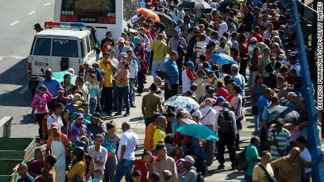 People queue outside Venezuela's Central Bank (BCV) in Caracas in an attempt to change 100 Bolivar notes, on December 16, 2016. Venezuelans lined up to deposit 100-unit banknotes before they turned worthless, but replacement bills had yet to arrive, increasing the cash chaos in the country with the world's highest inflation. Venezuelans are stuck in currency limbo after President Nicolas Maduro ordered the 100-bolivar note -- the largest denomination, currently worth about three US cents -- removed from circulation in 72 hours. / AFP / FEDERICO PARRA        (Photo credit should read FEDERICO PARRA/AFP/Getty Images)