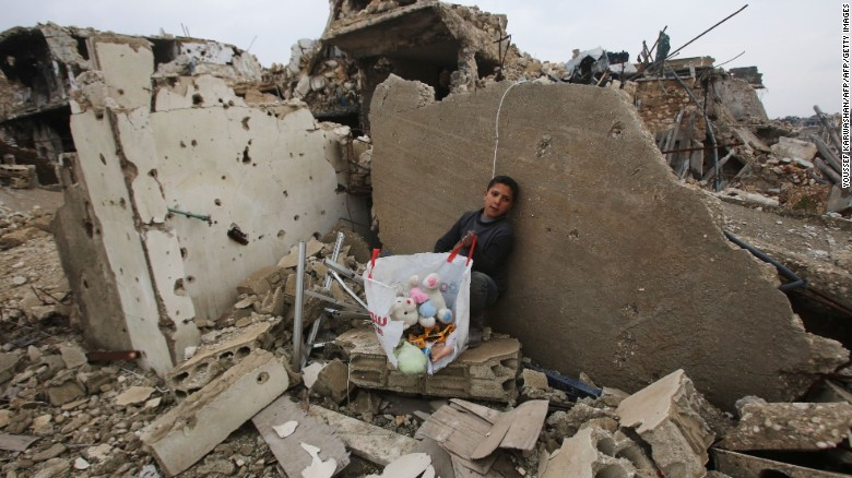 A boy sits with his belongings where his house once stood in Aleppo on December 17, 2016.
