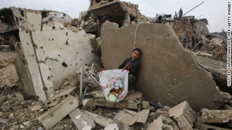 A Syrian boy with his belongings in the rubble of his home in Aleppo's Al-Arkoub neighborhood on Saturday.