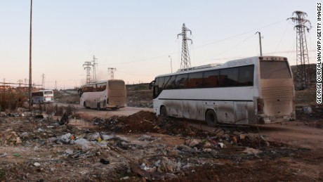Buses drive through the Syrian government-controlled crossing of Ramoussa, on the southern outskirts of Aleppo, on December 18, 2016, during an evacuation operation of rebel fighters and civilians from rebel-held areas. / AFP / George OURFALIAN        (Photo credit should read GEORGE OURFALIAN/AFP/Getty Images)