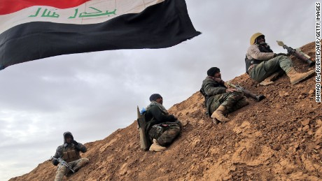 TOPSHOT - Shiite fighters from the Hashed al-Shaabi (Popular Mobilisation) paramilitary units sits under an Iraqi flag as they advance towards the village of Shwah, south of the city of Tal Afar on the western outskirts of Mosul, on December 13, 2016, during an ongoing operation against Islamic State (IS) group jihadists.Hashed al-Shaabi paramilitary forces said they retook three more villages southwest of Mosul, completing another phase in operations aimed at cutting the jihadists' link to Syria. / AFP / AHMAD AL-RUBAYE        (Photo credit should read AHMAD AL-RUBAYE/AFP/Getty Images)