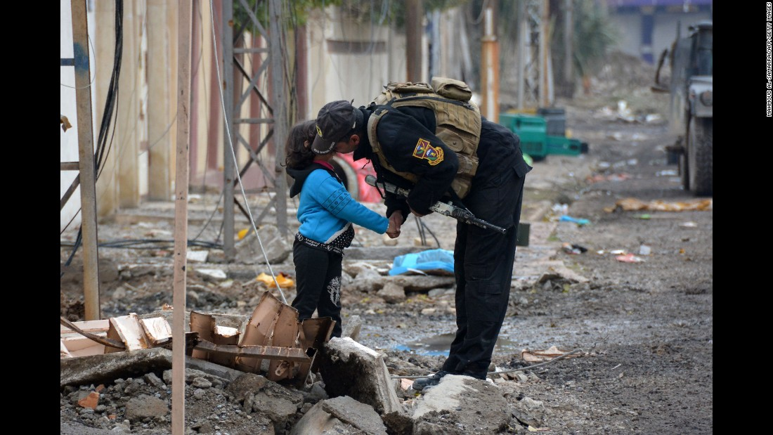 A member of Iraqi special forces kisses a child in the neighborhood of al-Barid east of Mosul on Sunday, December 18, during their ongoing operation to reclaim the city from Islamic State (ISIS) jihadists.