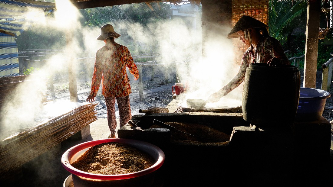 Vendors clean and prepare grain to be sold at the floating markets in the Mekong Delta.