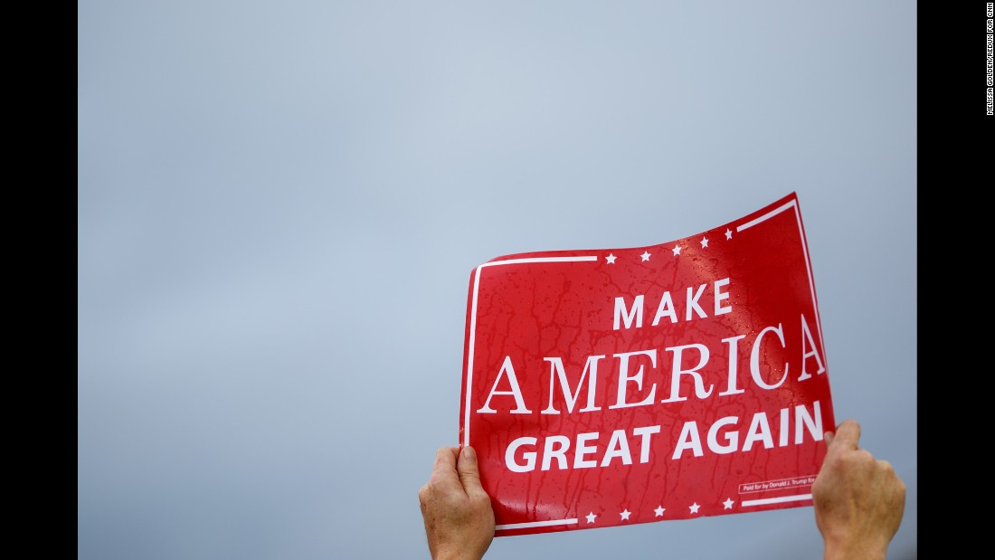 "A Trump supporter holds up a rain-soaked ""Make America Great Again"" sign."