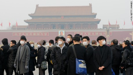 Tourists wearing masks visit the Tiananmen Square on December 18, 2016 in Beijing, China. At least 24 cities in North China issued red alerts on Friday as heavy smog will shroud the country's northern regions in the following two days.