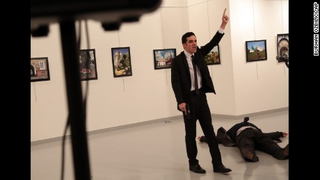 Karlov lies on the ground as a man with a pistol -- later identified as police officer Mevlut Mert Altintas -- gestures at the scene on December 19.