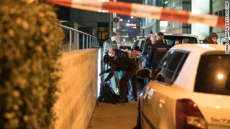 Policemen secure the area as the forensic team work, in front of the Islamic center, in Zurich, Monday, Dec. 19, 2016. A Zurich police official says a gunman has injured several people in Switzerland's largest city. The official said police were swarming to the scene in pursuit of the gunman who remains at large. (Ennio Leanza/Keystone via AP)