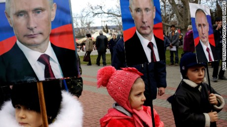 Children hold portraits of Putin during a rally to mark a Russian holiday -- Defender of the Fatherland day -- in the Crimean city of Sevastopol, on February 23, 2016.