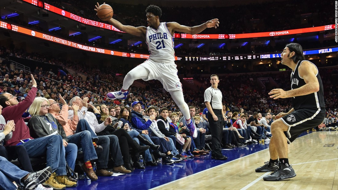 Joel Embiid, a center for the NBA's Philadelphia 76ers, dives into the crowd to keep a ball in play against Brooklyn on Sunday, December 18.
