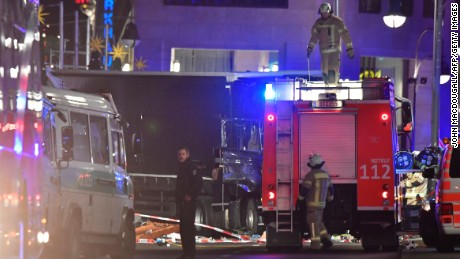 Rescue forces stand in front of the truck that speed into a Christmas market in Berlin, on December 19, 2016 killing nine persons and injuring at least 50 people. Ambulances and police rushed to the scene after the driver drove up the pavement of the market in a central square popular with tourists less than a week before Christmas, in a scene reminiscent of the deadly truck attack in Nice.