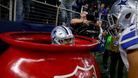 The Dallas Cowboys' Ezekiel Elliott celebrates in a Salvation Army kettle after scoring a touchdown Sunday.