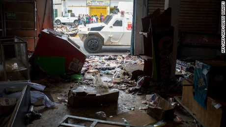 A Venezuelan National Guard vehicle is parked in front of a looted supermarket in Ciudad Bolivar, Bolivar state, Venezuela, on December 19, 2016. A jetload of new currency finally arrived in Venezuela on December 18 after its delayed arrival sparked protests and looting that jolted President Nicolas Maduro's unpopular government. / AFP / MANAURE QUINTERO        (Photo credit should read MANAURE QUINTERO/AFP/Getty Images)