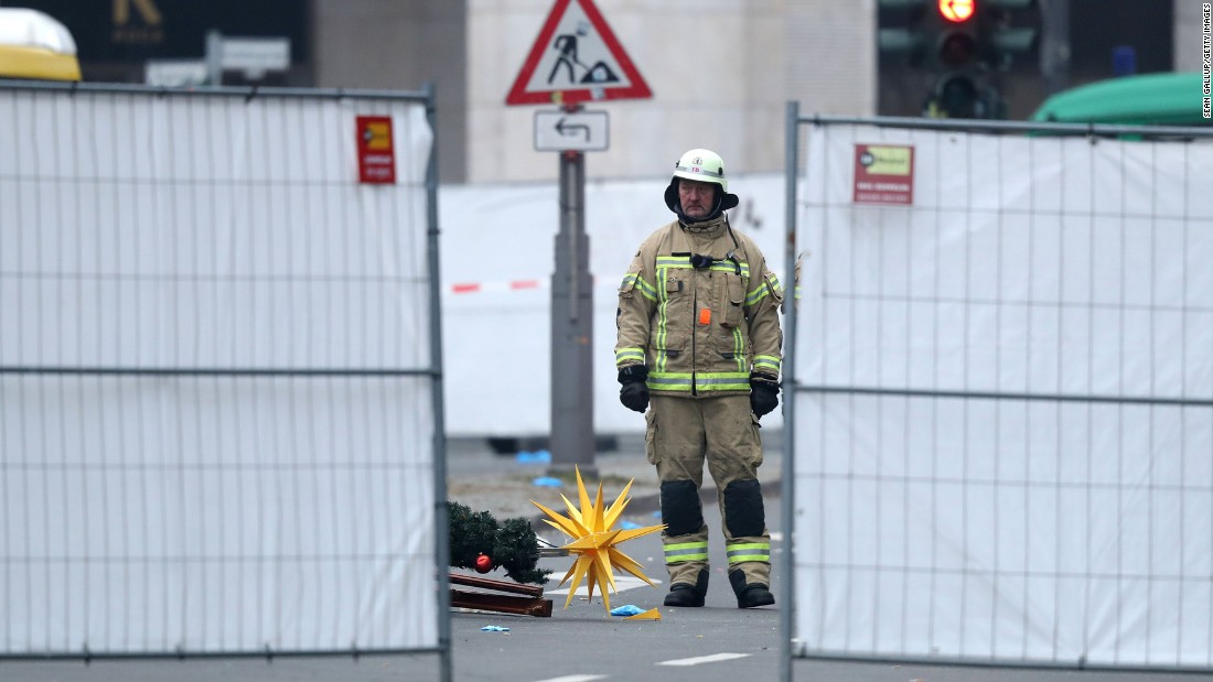 A rescue worker stands beside Christmas decorations that were scattered by the crash.