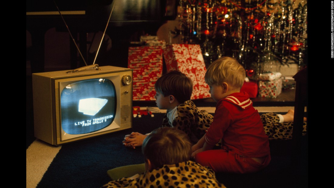 Boys in Virginia watch the Christmas Eve broadcast of Apollo 8, which orbited the moon in December 1968. Apollo 8 marked the first time that humans had ever left Earth's orbit, and millions around the world watched as the NASA spacecraft beamed back live images of the lunar surface.