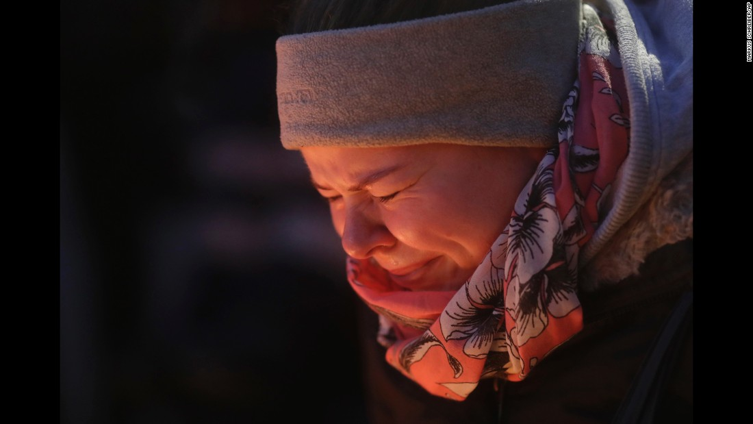 A woman is illuminated by candles as she cries in Berlin on December 20.