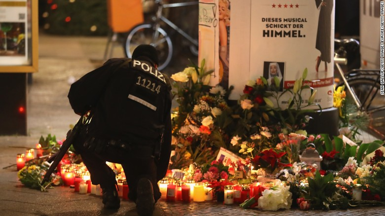 A policeman kneels at a memorial near the market.