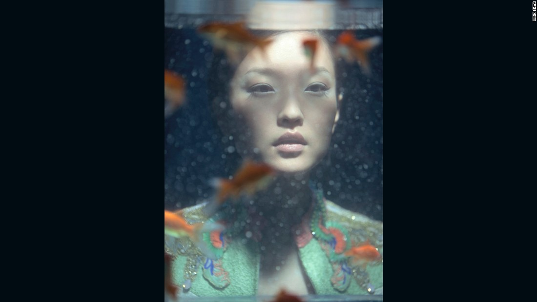 Supermodel Du Juan stares through a softly lit fish tank, lost in a pastel-colored soliloquy.