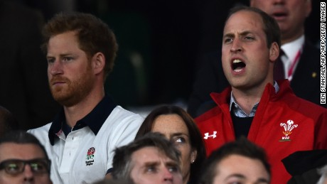 Prince Harry (L) and Prince William appear in the crowd wearing the shirts of opposing teams at the 2015 Rugby World Cup match between England and Wales.