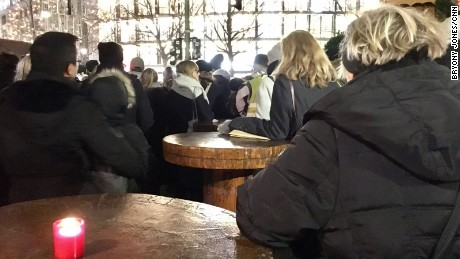 Mourners gather around tables at the closed Christmas market to listen to the service inside the Memorial Church.
