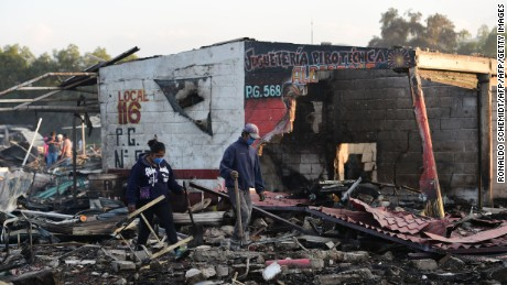 People search amid the debris left by a huge blast that occured in a fireworks market in Mexico City, on December 20, 2016 killing at least 26 people and injuring scores. The conflagration, in the suburb of Tultepec, set off a quickfire series of multicolored blasts and a vast amount of smoke that hung over Mexico City.  / AFP / RONALDO SCHEMIDT        (Photo credit should read RONALDO SCHEMIDT/AFP/Getty Images)