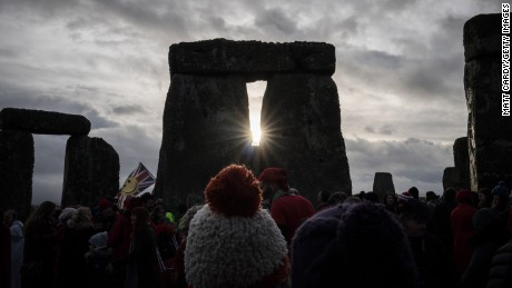 People look towards the sun as druids, pagans and revellers gather at Stonehenge, hoping to see the sun rise, as they take part in a winter solstice ceremony at the ancient neolithic monument of Stonehenge, UK.