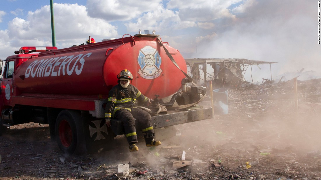 A firefighter rests on the back of a truck.