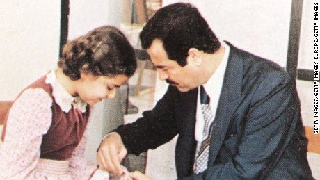 An undated photo of Saddam Hussein helping his daughter, Raghad, during a visit with family friends near Baghdad, Iraq.