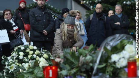 BERLIN, GERMANY - DECEMBER 21: Mourners lay flowers and candles at a makeshift memorial near the site where two days before a man drove a heavy truck into a Christmas market in an apparent terrorist attack on December 21, 2016 in Berlin, Germany. So far 12 people are confirmed dead and 48 injured. Authorities initially arrested a Pakistani man whom they believed was the driver of the truck, though later released him and are now pursuing other leads. Among the dead are a Polish man with a gunshot wound who was found on the passenger seat of the truck. Police are investigating the possibility that the truck, which belongs to a Polish trucking company, was hijacked the morning of the attack.  (Photo by Sean Gallup/Getty Images)