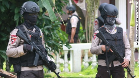 Armed police secure a house after alleged militants opened fire at officers in Tangerang, outside Jakarta, on December 21, 2016.