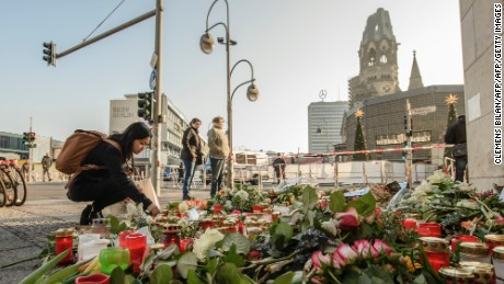A mourner places a candle on December 21, 2016 at a makeshift memorial near the Kaiser-Wilhelm-Gedaechtniskirche (Kaiser Wilhelm Memorial Church) in Berlin, close to the site where a truck crashed into a Christmas market two days before. Twelve people were killed and almost 50 wounded, 18 seriously, when the lorry tore through the crowd on December 19, 2016, smashing wooden stalls and crushing victims, in scenes reminiscent of July's deadly attack in the French Riviera city of Nice. / AFP / CLEMENS BILAN        (Photo credit should read CLEMENS BILAN/AFP/Getty Images)