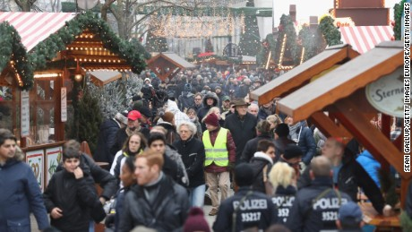 BERLIN, GERMANY - DECEMBER 22:  Visitors and police walk through the reopened Breitscheidplatz Christmas market only a short distance from where three days ago a truck plowed into the market, killed 12 people and injured dozens in a terrorist attack on December 22, 2016 in Berlin, Germany. The Breidscheidplatz Christmas market is reopening today, though its small amusement rides and bright lights displays will remain shut off in a sign of continuing mourning for the attack victims. Meanwhile police have launched a European-wide manhunt for Anis Amri, a 24-year-old Tunisian man they suspect of having driven the truck.  (Photo by Sean Gallup/Getty Images)