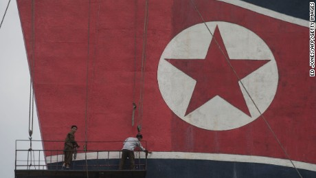 Workers paint a North Korean flag atop a building on Kim Il-Sung square on July 7, 2016. / AFP / Ed Jones        (Photo credit should read ED JONES/AFP/Getty Images)