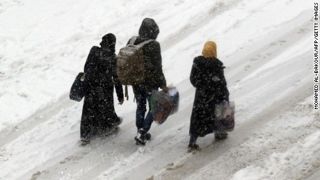 Displaced Syrians trudge through the snow with their belongings this week in Idlib province.