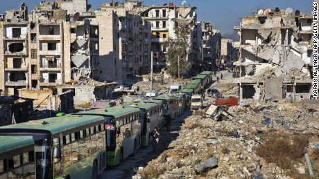 TOPSHOT - Buses are seen during an evacuation operation of rebel fighters and their families  from rebel-held neighbourhoods in the embattled city of Aleppo on December 15, 2016. A convoy of ambulances and buses left rebel territory in Aleppo in the first evacuations under a deal for opposition fighters to leave the city after years of fighting. The rebel withdrawal will pave the way for President Bashar al-Assad's forces to reclaim complete control of Syria's second city, handing the regime its biggest victory in more than five years of civil war.      / AFP / KARAM AL-MASRI        (Photo credit should read KARAM AL-MASRI/AFP/Getty Images)