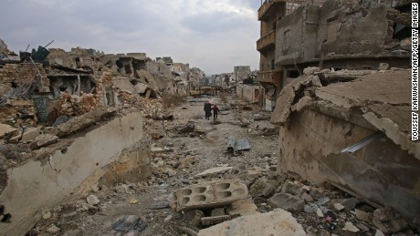 TOPSHOT - Syrians walk down a destroyed street in Aleppo's al-Akroub neighbourhood on December 17, 2016.  / AFP / Youssef KARWASHAN        (Photo credit should read YOUSSEF KARWASHAN/AFP/Getty Images)