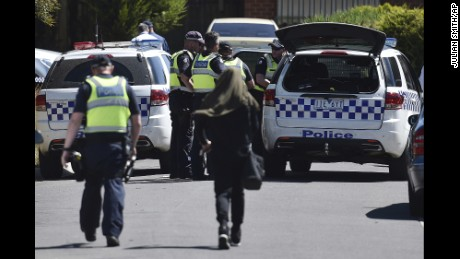 Police accompany a woman as they attend the scene where a house was raided at Meadow Heights in Melbourne, Australia, Friday, Dec. 23, 2016. Police in Australia detained five suspects who were allegedly planning a series of Christmas Day bomb attacks in the heart of the country's second largest city, officials said Friday. (Julian Smith/AAP Image via AP)