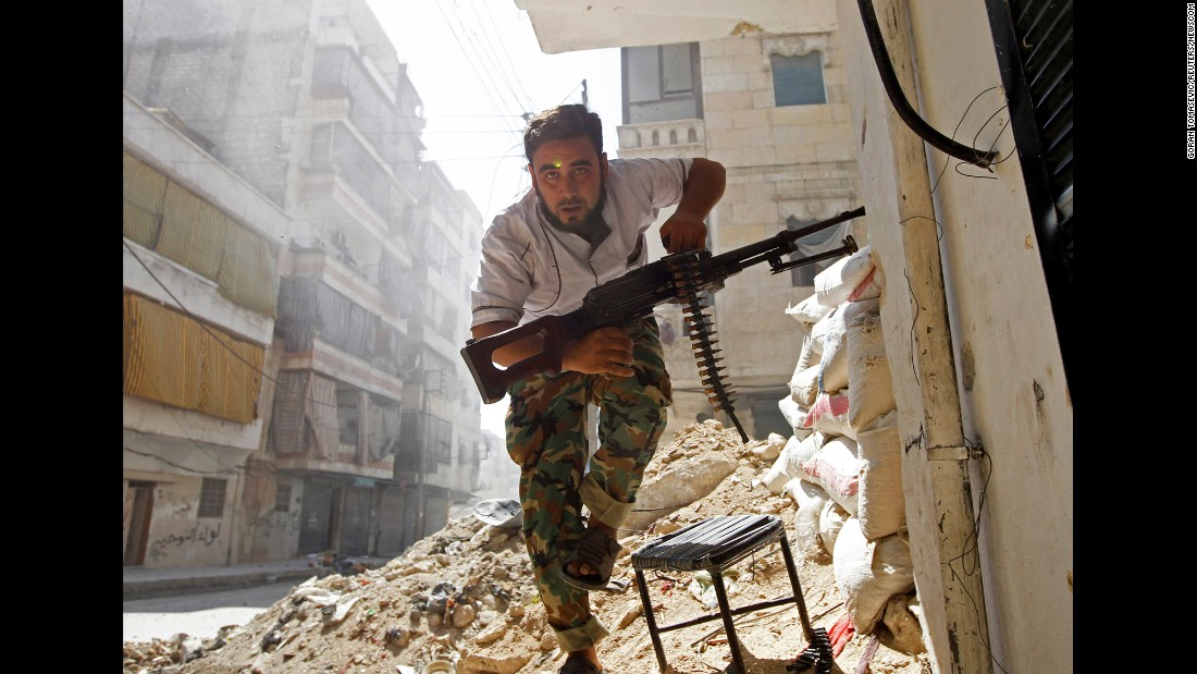 A Free Syrian Army fighter takes cover during clashes with Syrian army soldiers in the Salaheddine neighborhood of central Aleppo on August 7, 2012.