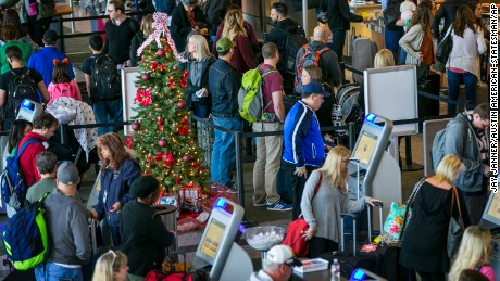 A Christmas tree is surrounded by travelers at the Southwest Airlines ticket counter on a busy day at Austin-Bergstrom International Airport in Austin, Texas, on Thursday, Dec. 22, 2016. (Jay Janner/Austin American-Statesman via AP)