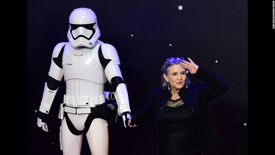 "Fisher salutes as she poses with a storm trooper at the European premiere of ""Star Wars: The Force Awakens"" in central London on December 16, 2015."